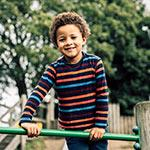 An image of a young boy smiling whilst on a climbing frame.